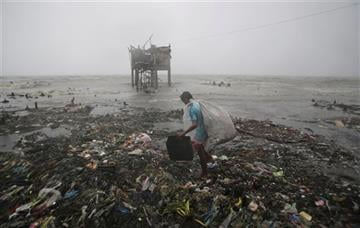 (AP Photo/Aaron Favila). A Filipino man scavenges recyclable materials near a house on stilts stands by the bay as strong winds and rains caused by Typhoon Koppu hit the coastal town of Navotas, north of Manila, Philippines Sunday, Oct. 18, 2015.