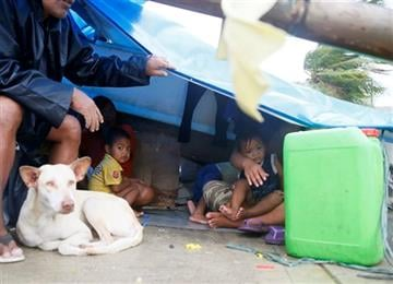(AP Photo/Bullit Marquez). A family seeks shelter under a plastic sheet by a concrete wall amid strong wind and a slight rain brought by Typhoon Koppu Sunday, Oct. 18, 2015 in Manila, Philippines.