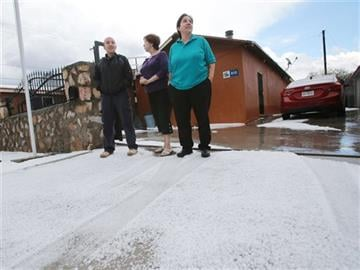 (Victor Calzada/The El Paso Times via AP). Cassandra Garcia, left, Linda Ramirez, center, and Melinda Ramirez took in the view of their hail-covered street after a storm Wednesday afternoon, Oct. 21, 2015, in El Paso, Texas.
