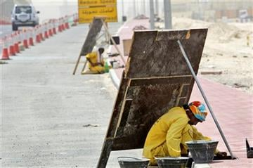 (AP Photo/Kamran Jebreili, File). FILE In this June 10, 2010 file photo, an Asian laborer avoids the direct sun by working behind a wooden sign, as he works on a manhole alongside of an under construction road in Dubai, United Arab Emirates.