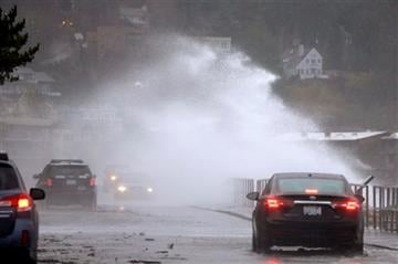 (AP Photo/Elaine Thompson). A wind-blown wave comes up and over the seawall and into traffic Tuesday, Nov. 17, 2015, in the West Seattle neighborhood of Seattle.