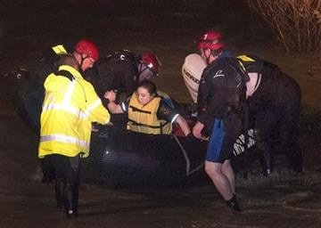 (FORT WORTH WEEKLY, 360 WEST). Firefighters assist Tarrant County Sheriff's Deputy Krystal Salazar after they rescued her from the raging waters of Deer Creek early Friday, Nov. 27, 2015, in Fort Worth, Texas.