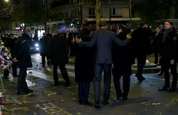 (Philippe Wojazer, Pool via AP). U.S. President Barack Obama, center, puts his arms around French President Francois Hollande and Paris Mayor Anne Hidalgo after paying their respect at the Bataclan concert hall, one of the recent deadly Paris attack sites