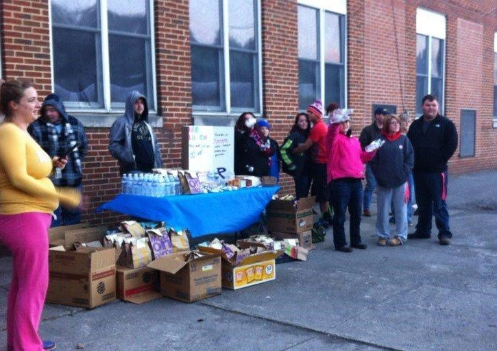 Parents hand out bagged lunches to students across the street from Richlands High School after an incident  that took place the day before in the school cafeteria.