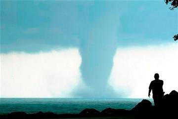 (AP Photo/The Kenosha News, Kevin Poirier). A person takes photos of a large water spout on Lake Michigan south east of Kenosha, Wis. on Thursday, Sept. 12, 2013.
