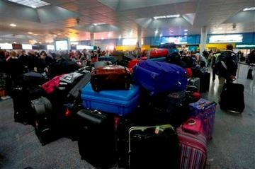 (AP Photo/Sang Tan). Luggage belonging to passengers piles up following a power outage at the North Terminal of London Gatwick Airport in Horley, England, Tuesday, Dec. 24, 2013.