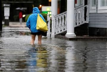 (AP Photo/Chuck Burton). A woman walks down a flooded sidewalk toward an open convenience store in Charleston, S.C., Sunday, Oct. 4, 2015.
