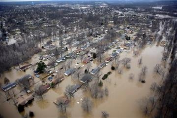 (AP Photo/Jeff Roberson, File). FILE - In this Dec. 31, 2015 file photo, houses are surrounded by floodwater in Arnold, Mo.